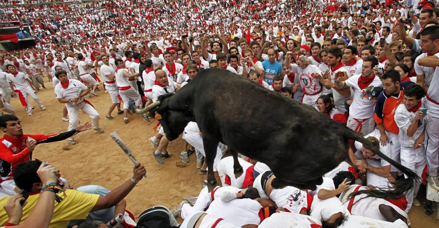 A cow jumps over revelers in a bullring during the second running of the bulls at the San Fermin fiestas, in Pamplona northern Spain, Sunday, July 8, 2012. (AP Photo/Ivan Aguinaga)